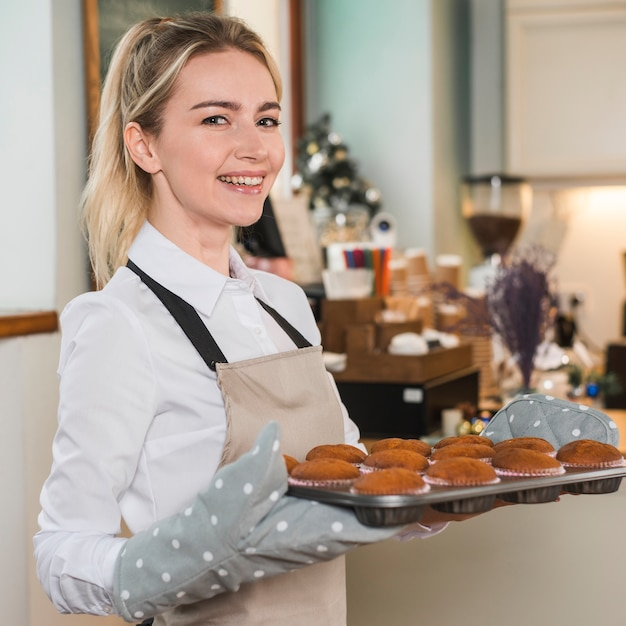 Portrait of a smiling female baker wearing mitt holding baked muffins in the tray Free Photo