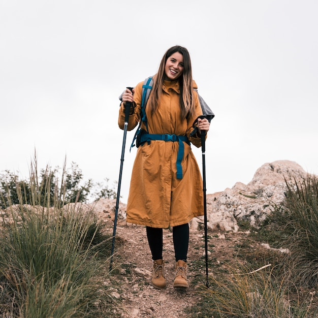 Portrait of a smiling female hiker holding hiking stick looking at camera Free Photo