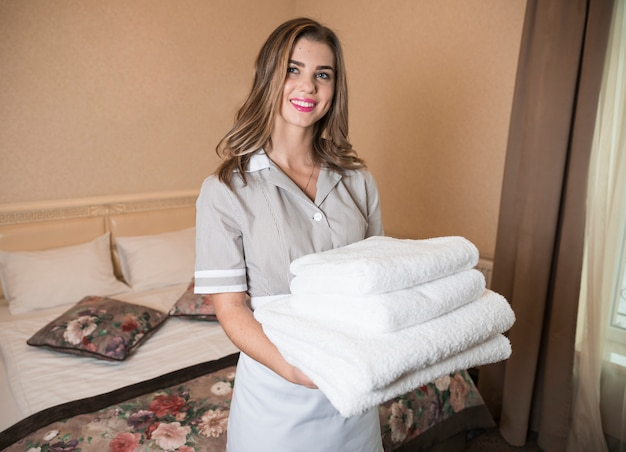 Portrait of smiling female maid holds a stacked of soft towels in the hotel room Free Photo