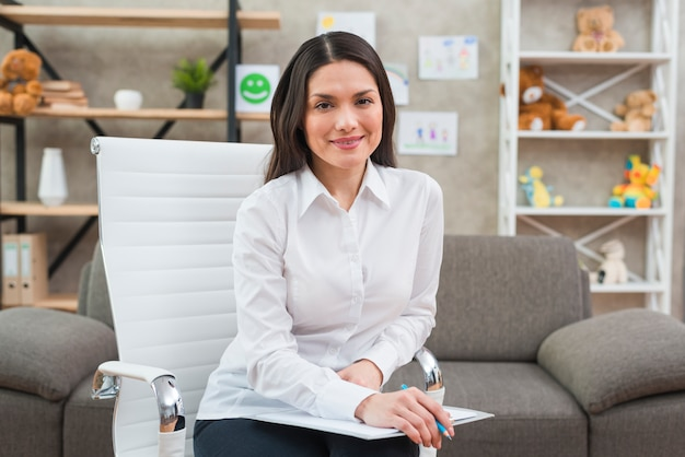 Portrait of a smiling female psychologist in her office Free Photo