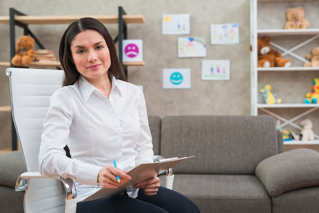 Portrait of smiling female psychologist sitting on white chair with clipboard and pencil in her office Free Photo