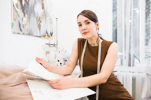 Portrait of a smiling female seamstress holding fashion sketch Free Photo
