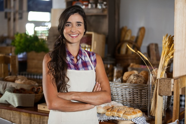 Portrait of smiling female staff standing with arms crossed at bakery shop Premium Photo