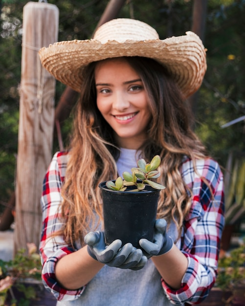 Portrait of a smiling female wearing gloves holding black cactus plant Free Photo