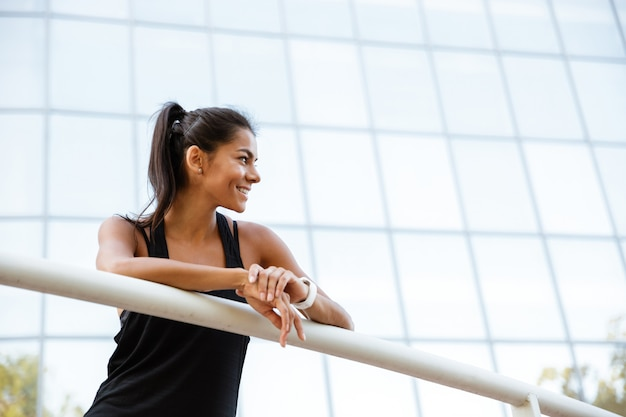 Portrait of a smiling fitness woman leaning on a rail Free Photo