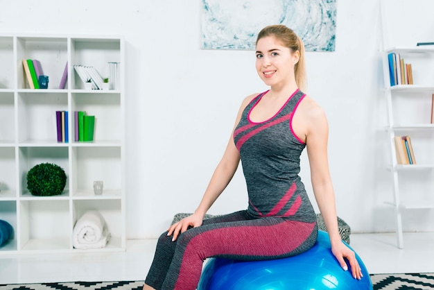 Portrait of a smiling fitness young woman sitting on blue pilates ball looking at camera Free Photo