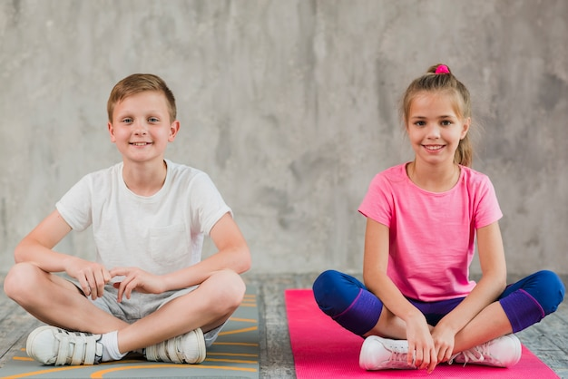 Portrait of a smiling girl and boy sitting on exercise mat with their crossed legs in front of wall Free Photo