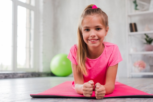 Portrait of a smiling girl exercising on pink mat Free Photo