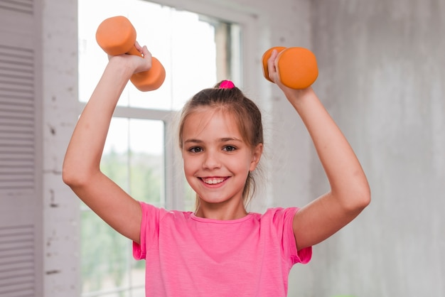 Portrait of a smiling girl exercising with an orange dumbbell Free Photo