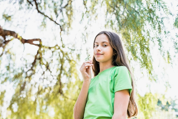 Portrait of a smiling girl holding fern in hand looking at camera standing under the tree Free Photo