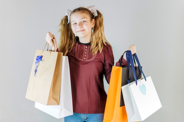 Portrait of a smiling girl holding shopping bags Free Photo