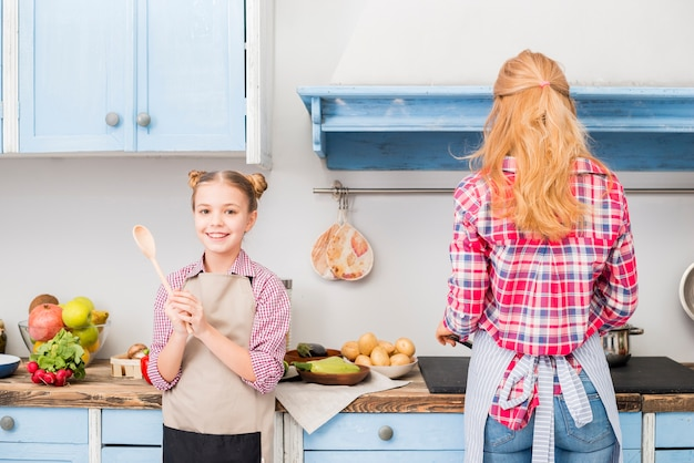 Portrait of a smiling girl holding spoon in hand and her mother cooking food in the kitchen Free Photo