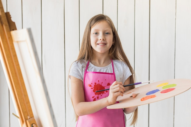 Portrait of a smiling girl holding wooden palette and paintbrush standing against white wooden wall Free Photo