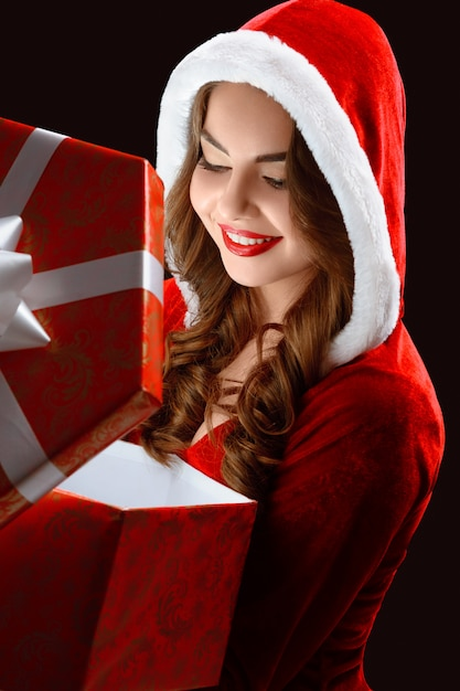 Portrait of smiling girl in the red suit,opening a gift for new year Free Photo