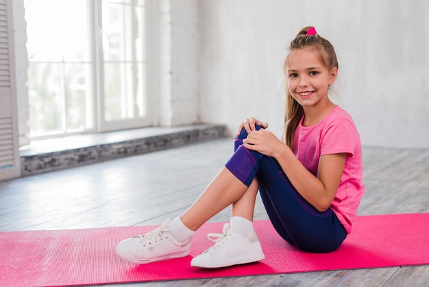 Portrait of a smiling girl sitting on exercise mat with her crossed legs Free Photo