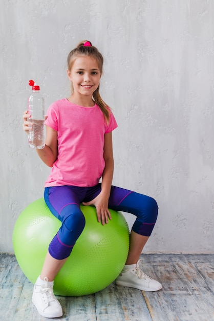 Portrait of a smiling girl sitting on green pilates holding plastic water bottle in hand Free Photo