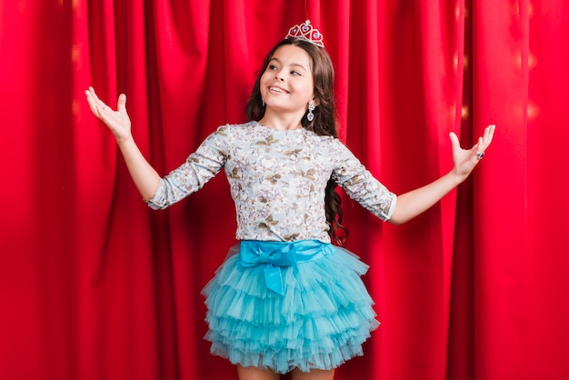 Portrait of a smiling girl standing behind the red curtain shrugging Free Photo