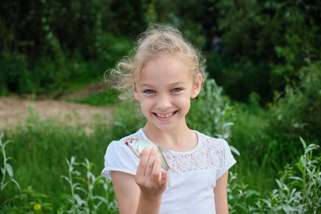 Portrait of a smiling girl with a silver fish in her hands on the space of green nature. Premium Photo