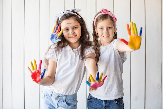 Portrait of smiling girls wearing headband showing colorful painted hands against wooden wall Free Photo