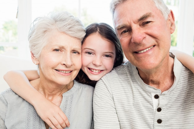 Portrait of smiling grandparents and granddaughter on the sofa Premium Photo