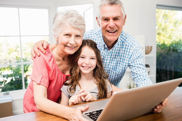 Portrait of smiling grandparents and granddaughter using laptop at home Premium Photo