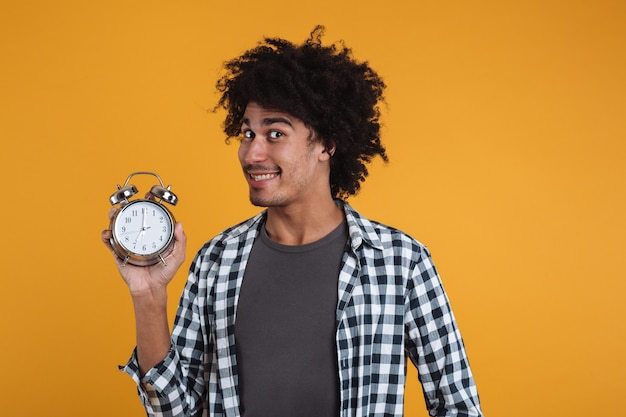 Portrait of a smiling happy african man showing alarm clock Free Photo