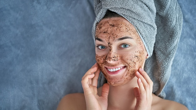 Portrait of smiling healthy female in bath towel with natural cleansing face coffee scrub after shower Premium Photo