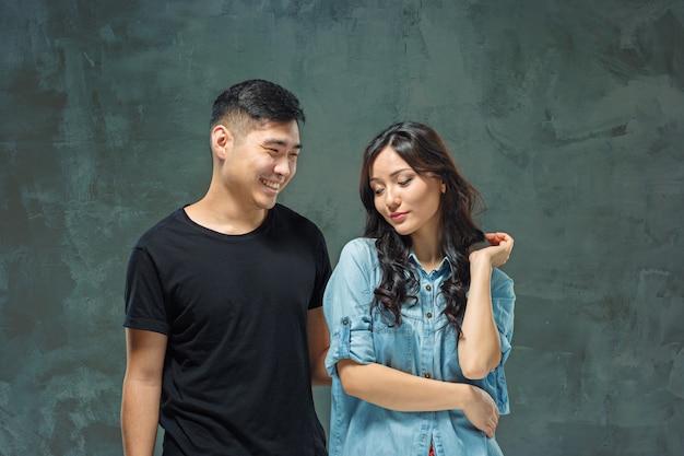 Ritratto delle coppie coreane sorridenti su una parete grigia Foto Gratuite