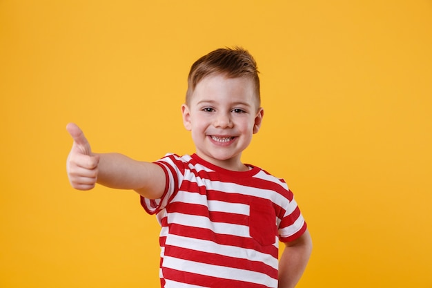 Portrait of a smiling little boy showing thumbs up Free Photo