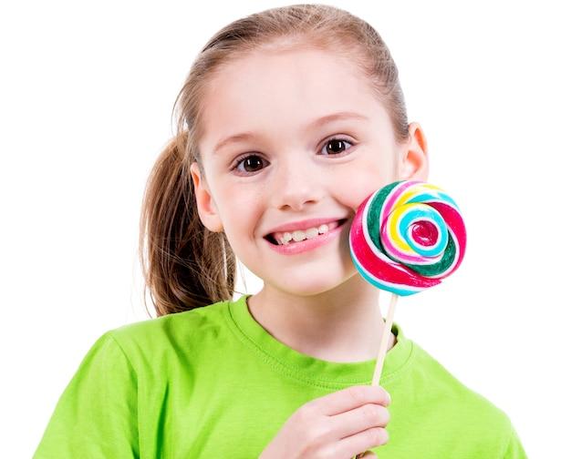 Ritratto di bambina sorridente in maglietta verde con caramelle colorate - isolato su bianco. Foto Gratuite