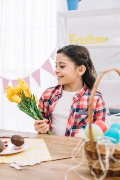 Portrait of a smiling little girl holding yellow tulip flowers on easter day Free Photo