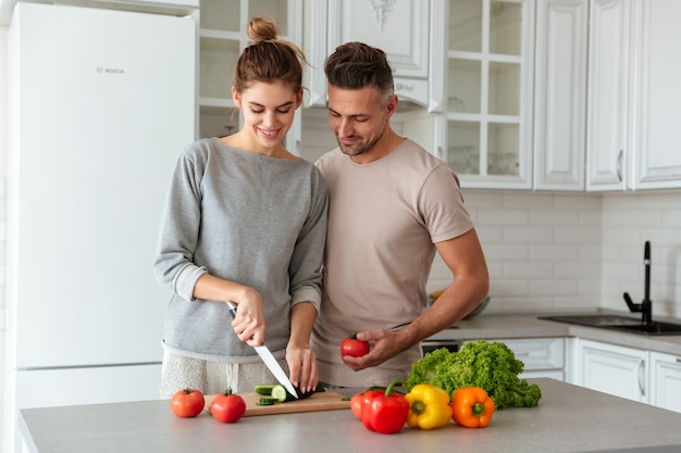 Portrait of a smiling loving couple cooking salad Free Photo