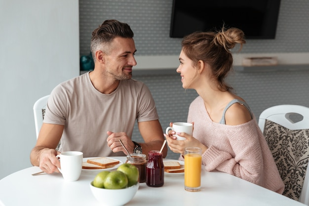 Portrait of a smiling loving couple having breakfast Free Photo