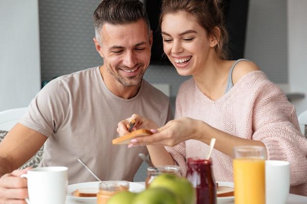 Portrait of a smiling loving couple having breakfast Free Photo