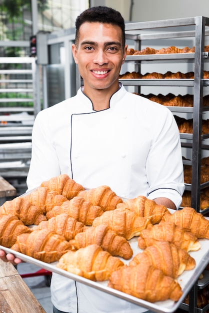 Portrait of a smiling male baker holding tray of baked croissant Free Photo