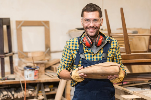 Portrait of smiling male carpenter holding incomplete wooden model Free Photo