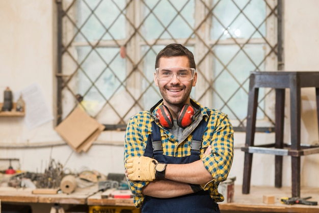 Portrait of a smiling male carpenter standing in front of workbench Free Photo