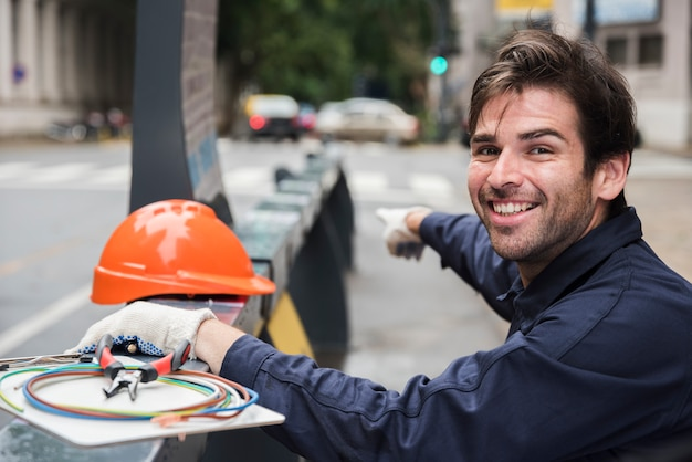 Portrait of smiling male electrician pointing with hard hat and equipment on street Free Photo