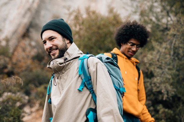 Portrait of a smiling male hiker hiking with his friend Free Photo