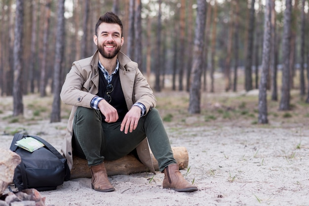 Portrait of a smiling male traveler sitting on beach with his backpack Free Photo