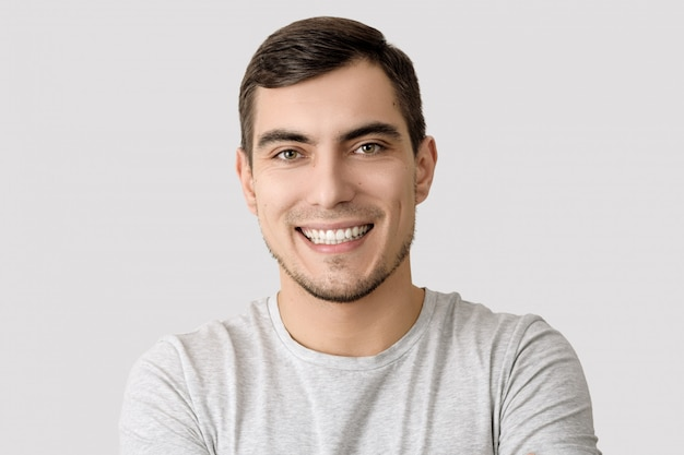 Portrait of smiling man in gray t-shirt on light background for advertising Premium Photo