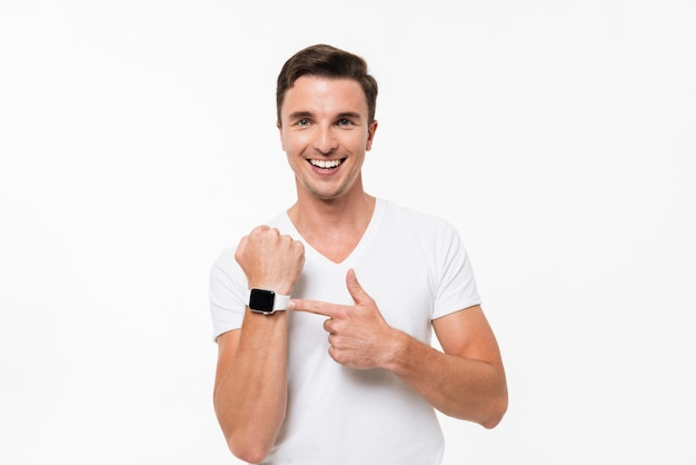 Portrait of a smiling man pointing finger at smart watch Free Photo