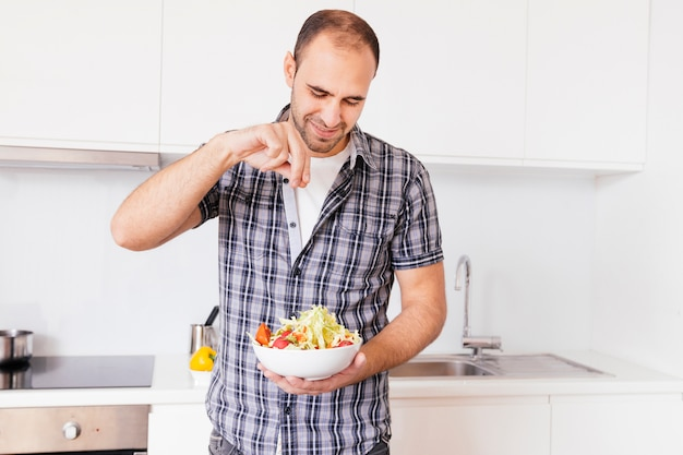 Portrait of a smiling man seasoning the salt on salad in the kitchen Free Photo