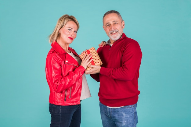 Portrait of smiling mature man giving present to his wife in red jacket Free Photo