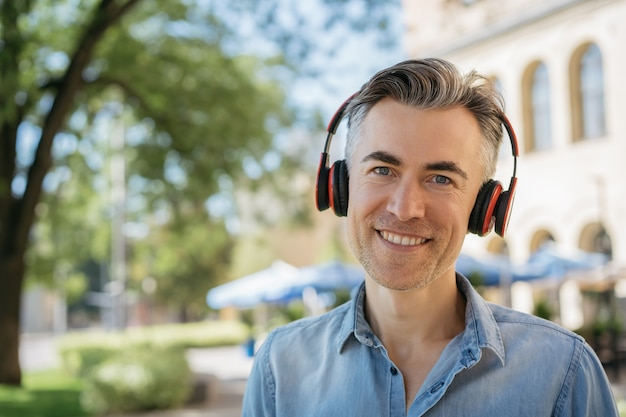 Portrait of smiling mature man listening to music wearing red headphones Premium Photo