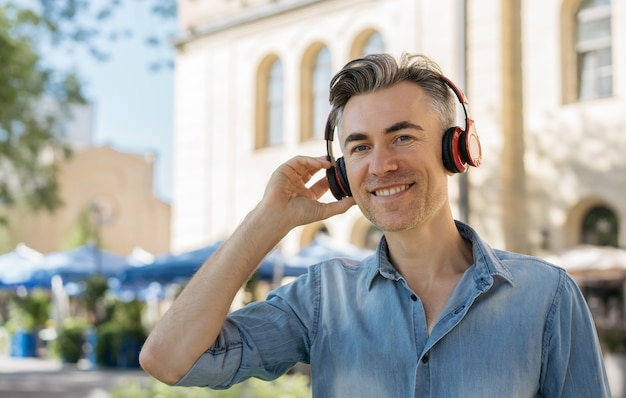 Portrait of smiling mature man listening to music Premium Photo