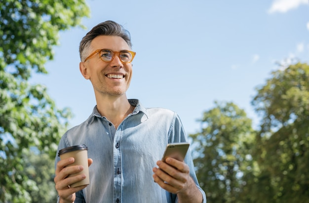 Portrait of smiling mature man wearing stylish eyeglasses walking in park Premium Photo