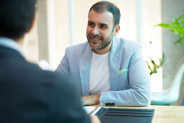 Portrait of smiling mid adult businessman sitting in office Free Photo