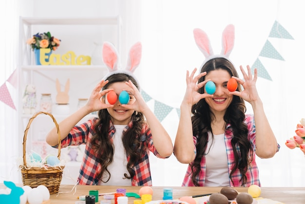 Portrait of smiling mother and her daughter covering their eyes with easter eggs Free Photo