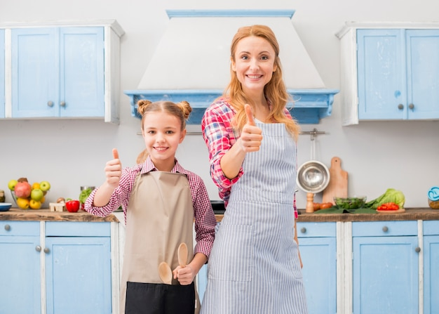 Portrait of a smiling mother and her daughter showing thumb up sign in the kitchen Free Photo